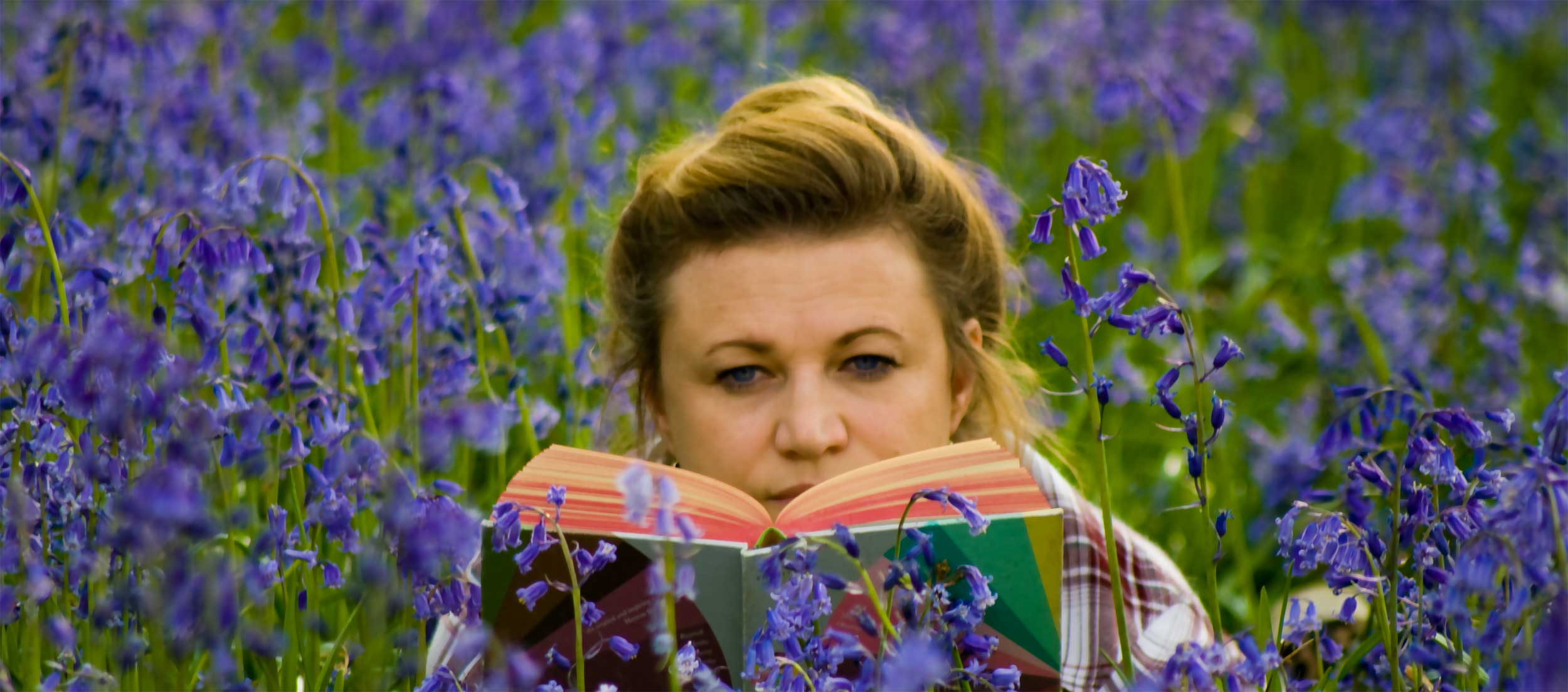 Juanita reading in the bluebell wood
